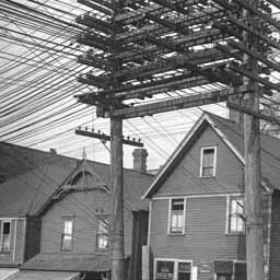 Telephone poles with massive clusters of wires like this were common at the time. This is a street corner in Vancouver in the thirties.